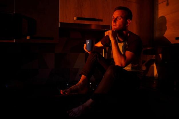 Ein mann sitzt im abendlicht in der küche und trinkt kaffee
