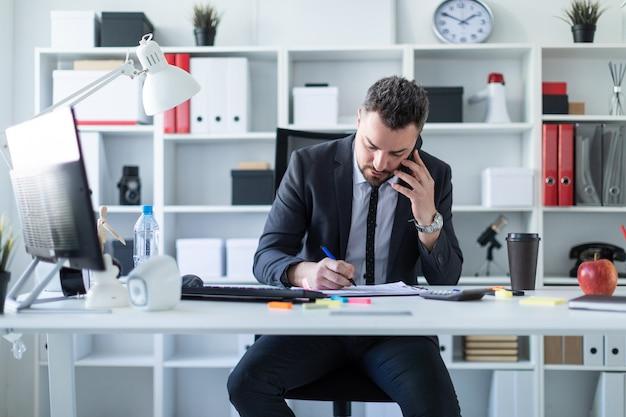 Ein mann sitzt im büro am tisch, telefoniert und arbeitet mit dokumenten.
