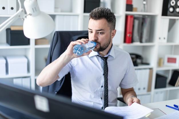 Ein mann sitzt im büro an einem tisch, arbeitet mit dokumenten und trinkt wasser aus einer flasche.