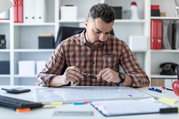 Ein mann sitzt im büro an einem tisch und betrachtet die grafik auf einer magnettafel.