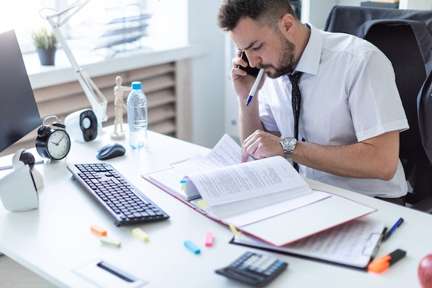 Ein mann sitzt im büro, arbeitet mit dokumenten, hält einen marker im mund und telefoniert.