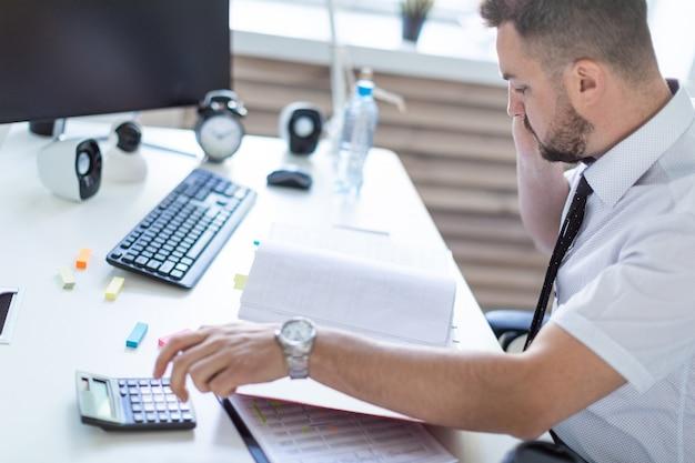 Ein mann sitzt im büro, arbeitet mit dokumenten und telefoniert.