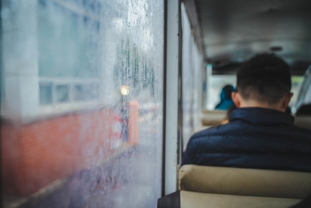 Ein mann sitzt im bus neben einem glasfenster