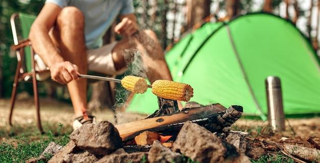 Ein mann sitzt in der nähe eines zeltes am lagerfeuer und brät über das wochenende mais am spieß in einem kiefernwald. camping, erholung, wandern.