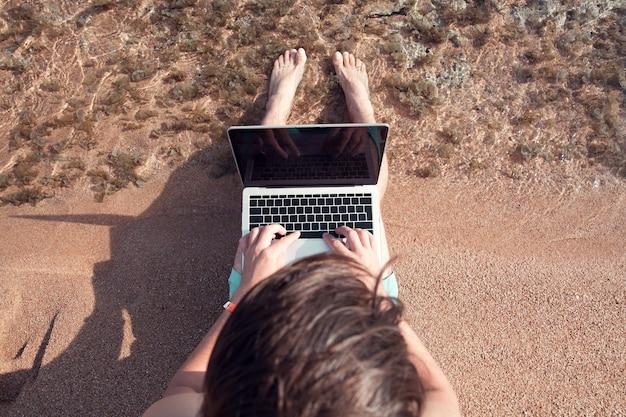 Ein mann sitzt mit einem laptop auf einem sand und arbeitet als freiberufler