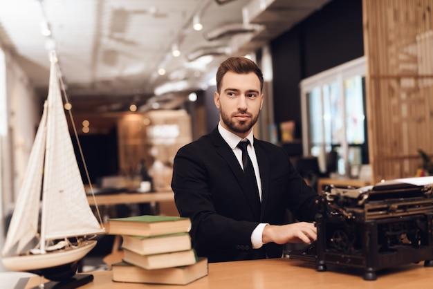 Ein mann sitzt mit einer alten schreibmaschine an einem tisch.