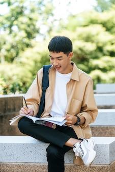 Ein mann sitzt und liest ein buch auf der treppe.