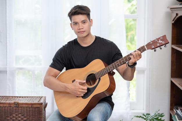 Ein mann sitzt und spielt gitarre auf einem stuhl.