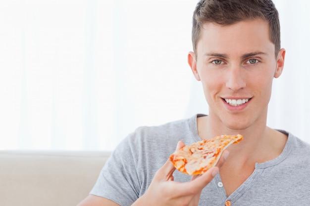 Ein mann sitzt, wie er ein stück pizza hält