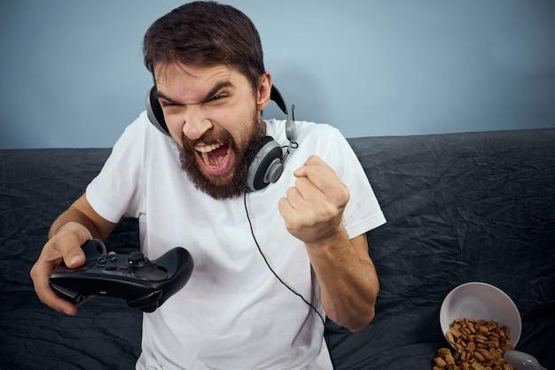 Ein mann spielt ein computerspiel in konsolen mit joysticks in kopfhörern auf einem sofa zu hause