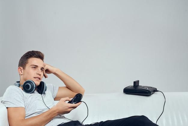 Ein mann spielt ein computerspiel in konsolen mit joysticks in kopfhörern mit einem laptop zu hause auf der couch