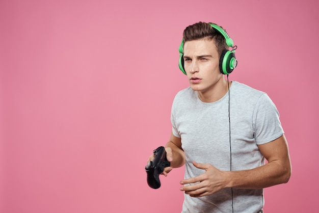 Ein mann spielt ein computerspiel in konsolen mit joysticks in kopfhörern mit einem laptop