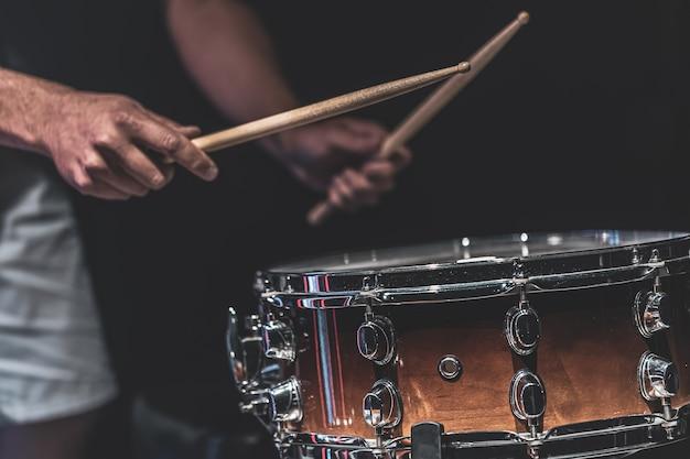 Ein mann spielt eine kleine trommel mit stöcken, ein schlagzeuger spielt ein schlaginstrument, nahaufnahme. Kostenlose Fotos