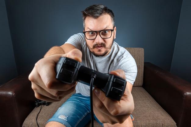 Ein mann spielt eine videospielkonsole, während er auf einem sofa sitzt. ruhetag, unterhaltung, freizeit.