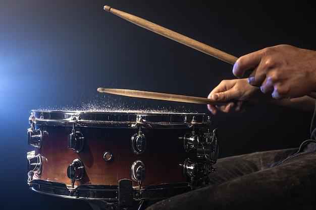 Ein mann spielt mit drumsticks auf einer snare-drum mit spritzwasser.