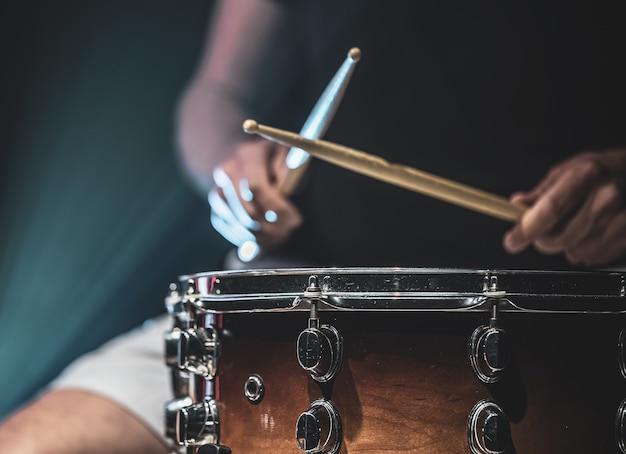 Ein mann spielt mit stöcken auf einer trommel, ein schlagzeuger spielt ein schlaginstrument, kopierraum.