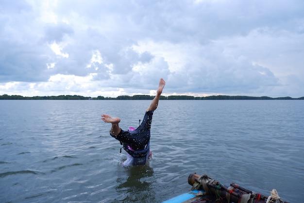Ein mann springt mit seltsamer haltung von einem hausboot ins meer.
