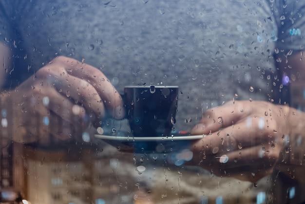 Ein mann steht am fenster und trinkt kaffee. regentropfen auf glas.