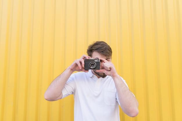 Ein mann steht an einer gelben wand und macht ein foto auf einer retro-kamera.