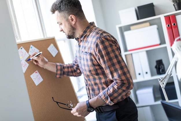 Ein mann steht im büro neben dem fenster und schreibt einen marker auf die aufkleber.