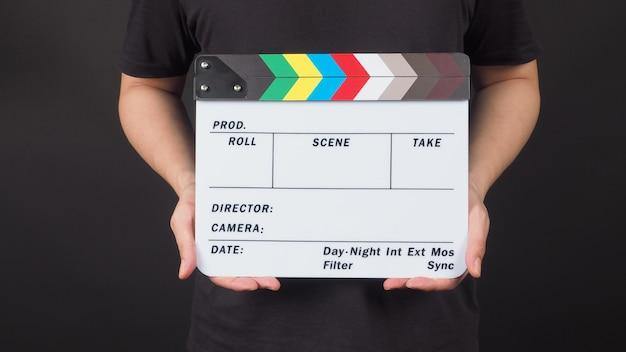 Ein mann steht mit den händen hält clapperboard oder filmschiefer. es ist schwarzer hintergrund.