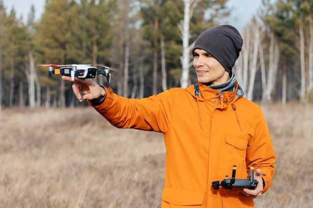 Ein mann steuert eine quadcopter-drohne im freien im herbst. der mann streckt der drohne die hand entgegen.