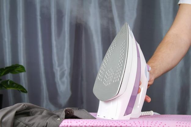 Ein mann streichelt leinen mit einem elektrischen bügeleisen auf einem bügelbrett.