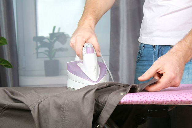 Ein mann streichelt leinen mit einem schwarzen elektrischen bügeleisen auf einem bügelbrett.