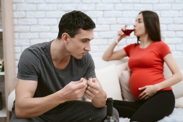Ein mann streitet sich mit einem schwangeren mädchen, das alkohol trinkt.