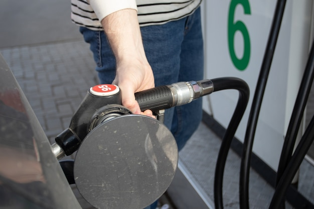 Ein mann tankt das auto an einer tankstelle. tankstelle. zapfsäule hautnah. ein auto wird mit einer benzinpistole betankt.