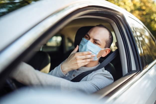 Ein mann taxifahrer fährt ein auto und passt die medizinische maske während des ausbruchs des coronavirus an.