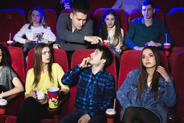 Ein mann telefoniert laut in einem kino und verhindert, dass sie einen film sehen. der mann macht eine bemerkung und bittet, das telefon auszuschalten