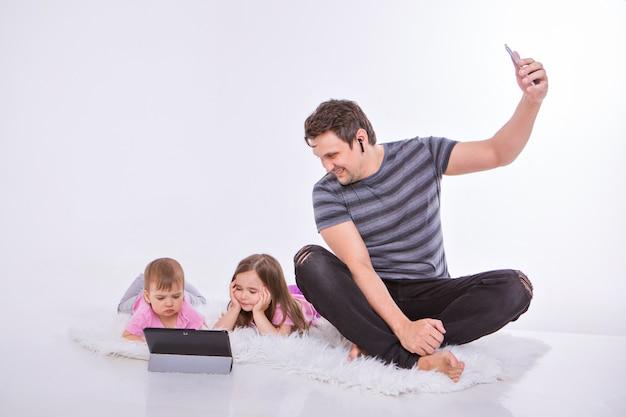 Ein mann telefoniert über ein headset, kinder sehen sich einen cartoon auf einem tablet an.