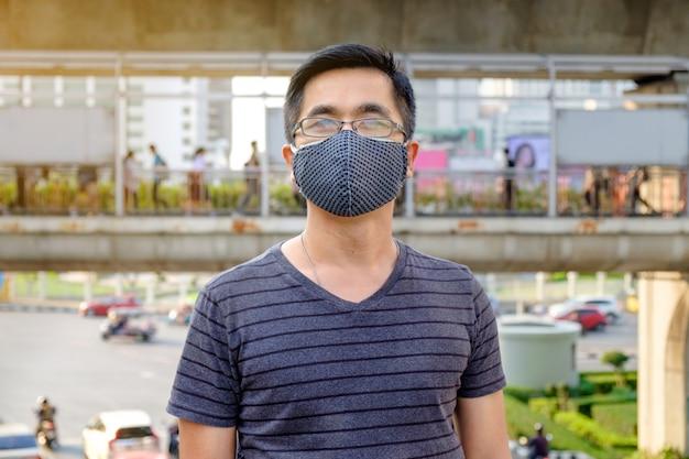 Ein mann trägt eine brille und eine schwarze mundmaske gegen luftverschmutzung mit pm 2.5 in bangkok thailand