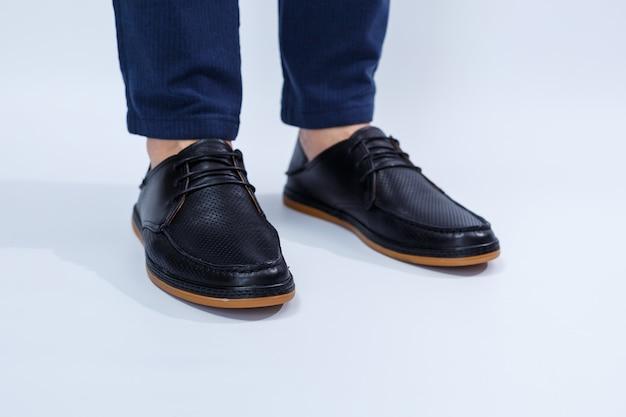 Ein mann trägt klassische schwarze schuhe aus naturleder auf spitze, schuhe für herren im business-stil