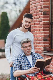 Ein mann trägt seinen vater in der nähe eines pflegeheims, sie haben spaß und lachen beim lesen eines buches