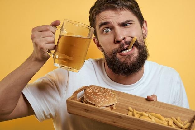 Ein mann trinkt bier aus einem glas und isst fast food