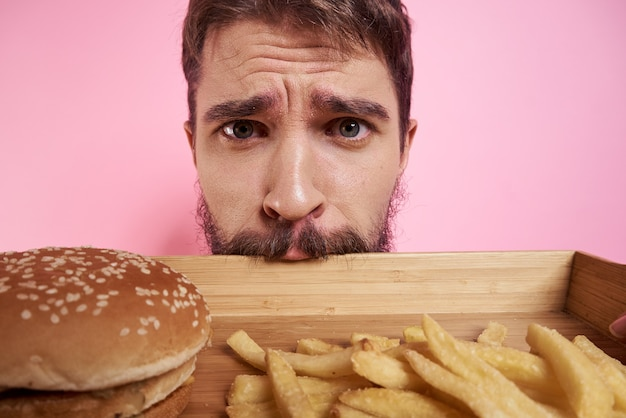 Ein mann trinkt bier aus einem glas und isst junk-gebratenes fast food