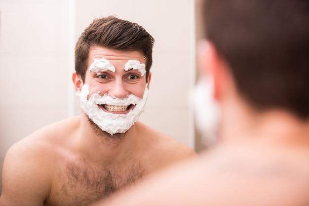 Ein mann trug rasierschaum auf sein gesicht auf.