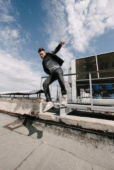 Ein mann übt parkour, rennt und springt über hindernisse