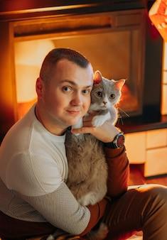 Ein mann umarmt eine katze fest, während er auf dem boden neben dem kamin sitzt
