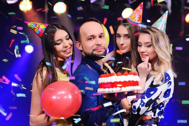 Ein mann und drei mädchen freuen sich und feiern die party im nachtclub