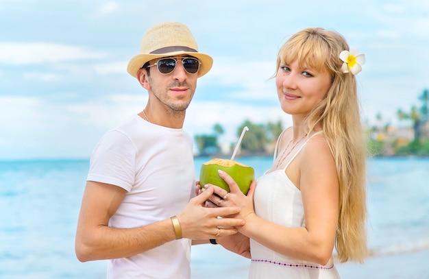 Ein mann und ein mädchen am strand trinken kokosnuss.