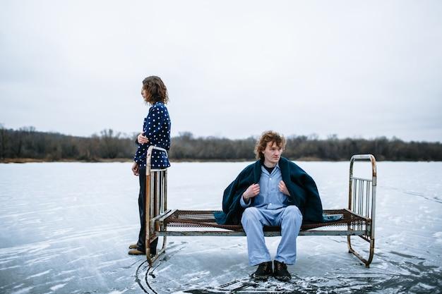 Ein mann und ein mädchen im pyjama auf dem eis eines zugefrorenen sees