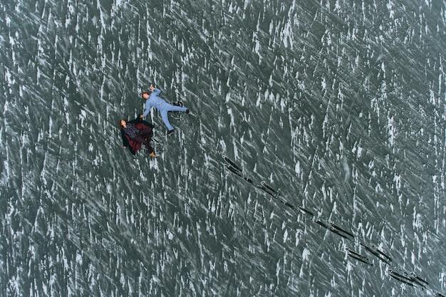 Ein mann und ein mädchen im schlafanzug liegen auf dem eis eines zugefrorenen sees