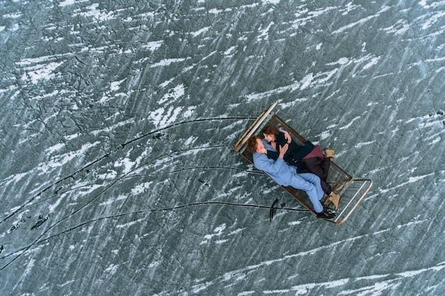Ein mann und ein mädchen im schlafanzug liegen auf einem eisenbett auf dem eis eines zugefrorenen sees