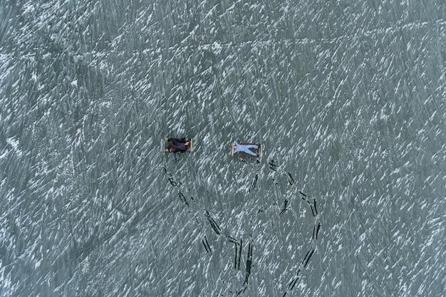 Ein mann und ein mädchen im schlafanzug liegen auf eisenbetten auf dem eis eines zugefrorenen sees