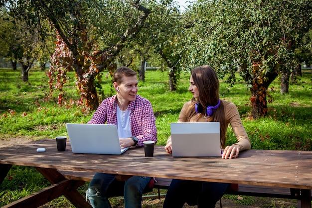Ein mann und ein mädchen sitzen an einem holztisch im park und arbeiten mit kopfhörern an laptops. freiberufliche tätigkeit im freien. arbeiten außerhalb des büros aufgrund der covid-19-pandemie