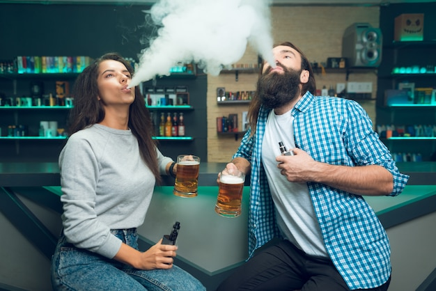 Ein mann und ein mädchen sitzen mit einem bier in der hand.