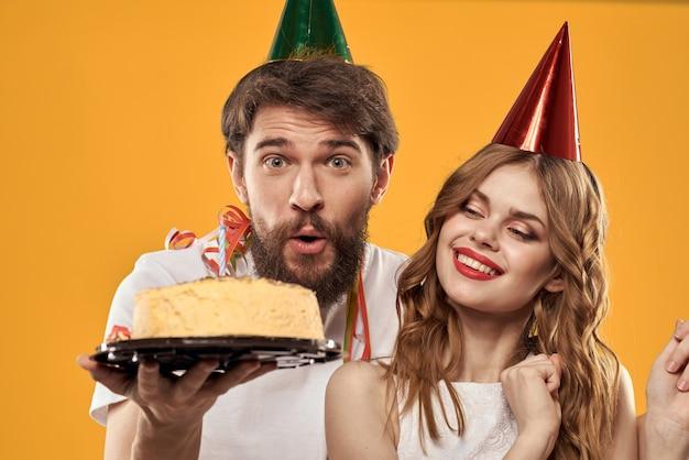 Ein mann und eine frau an einem geburtstag mit einem cupcake und einer kerze in einer festlichen mütze haben spaß und feiern gemeinsam den urlaub, glückliches paar